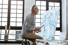 Famous modern artist using shades of blue in his new masterpiece. Shades of blue. Famous modern artist wearing glasses using shades of blue in his new stock images