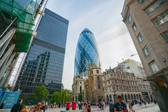 Famous modern London buildings surrounded by traditional low-rise buildings and people on street below royalty free stock photo
