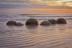 Famous Moeraki Boulders in South Island of New Zealand. Touristic place, sunset at coast line royalty free stock images