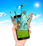 Famous monuments of the world going out of a mobile phone Royalty Free Stock Photography