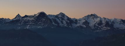 Famous mountains Eiger Monch and Jungfrau at sunrise Stock Image