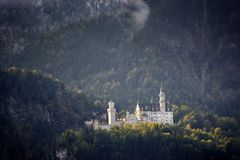 The famous Neuschwanstein Castle in the background of snowy mountains and trees with yellow and green leaves. Bavaria, Germany. stock photo