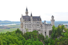 Famous Neuschwanstein Castle overlooking the surrounding valley and meadow, Royalty Free Stock Images