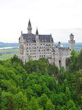 Famous Neuschwanstein Castle overlooking the surrounding valley and meadow Stock Photo