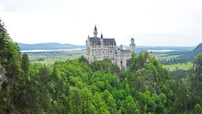 Famous Neuschwanstein Castle overlooking the surrounding valley and meadow, in Schwangau Stock Images