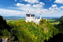 Famous Neuschwanstein Castle, 19th-century Romanesque Revival palace on a rugged hill above the village of Hohenschwangau in south. Famous Neuschwanstein Castle royalty free stock photos
