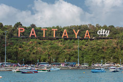 The famous Pattaya city sign on the hill at Pattaya bay with commerical boats and speed boats. Pattaya, Thailand - March 7, 2017 : The famous Pattaya city sign royalty free stock photography