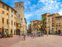 Famous Piazza della Cisterna in historic San Gimignano, Tuscany, Italy. Panoramic view of famous Piazza della Cisterna in the historic town of San Gimignano on a royalty free stock image