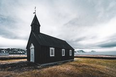 Famous picturesque black church of Budir at Snaefellsnes peninsula region in Iceland during a heavy snowy weather stock photo