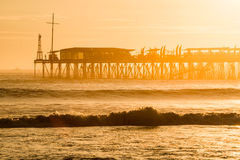 Famous pier at Pimentel. Peru. Sunset on the Pacific Ocean, the sun breaks through the mist and famous pier at Pimentel. Peru, Latin America Royalty Free Stock Photos