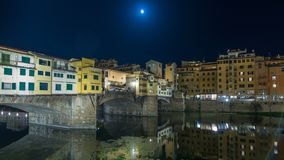 Famous Ponte Vecchio bridge timelapse hyperlapse over the Arno river in Florence, Italy, lit up at night. Full moon. Reflection on water. Old houses on the stock footage