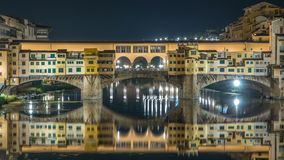Famous Ponte Vecchio bridge timelapse over the Arno river in Florence, Italy, lit up at night. Reflection on water. Old houses on the side stock video