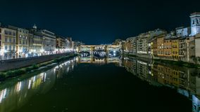 Famous Ponte Vecchio bridge timelapse over the Arno river in Florence, Italy, lit up at night. Reflection on water. Old houses on the side stock video footage