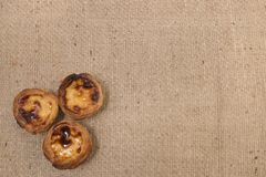 Famous Portuguese egg pastry tart. Called 'Pastel de Belem' on hessian fabric Royalty Free Stock Photography