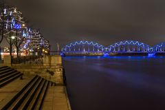 Famous railway bridge across Daugava river at night in Riga. stock photo
