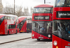 The famous red London buses on the streets of London city. Houses of Parliament in background Stock Photography