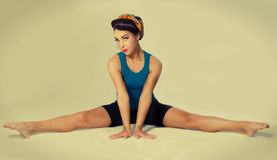 Famous retro pose foto. Brunette in a blue shirt with a scarf on her head and hair in a retro style sitting on the splits Royalty Free Stock Photo