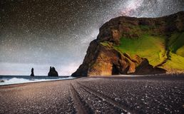 Famous Reynisdrangar rock formations at black Reynisfjara Beach. Coast of the Atlantic ocean near Vik, southern Iceland. Fantastic starry sky and the milky way stock images