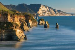 Famous rocks `Three Sisters` on the Pacific coast. North Island, New Zealand. The concept of ecological, active and phototourism. stock images