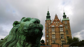 The famous Rosenborg castle in Central Copenhagen. Lion statue in focus in the foreground Denmark Royalty Free Stock Images