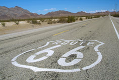 Famous Route 66. Long road with a Route 66 sign painted on it Royalty Free Stock Image