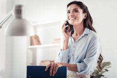 Famous smiling designer discussing new fabrics by the phone royalty free stock images