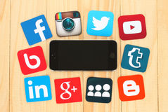 Famous social media icons placed around iPhone on wooden background. KIEV, UKRAINE - JULY 01, 2015: Famous social media icons such as: Facebook, Twitter, Blogger stock photo