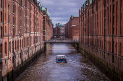 Famous Speicherstadt Warehouse District with Dark Clouds in Hamburg, Germany. Tourist boat in famous Speicherstadt warehouse district with dark clouds in Hamburg Royalty Free Stock Photography
