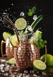Famous splashing Moscow mule alcoholic cocktail in copper mugs. Famous splashing Moscow mule alcoholic cocktail in copper mugs, freeze motion effect stock photography