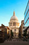 The famous St Paul`s cathedral at sunrise, London, United Kingdom. St Paul`s cathedral seen from a narrow alley enclosed by glass and brick buildings in the Royalty Free Stock Photography