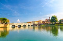 Famous stone arch Tiberius bridge Ponte di Tiberio Augustus over Marecchia river water, old buildings houses in Rimini. Famous stone arch Tiberius bridge Ponte royalty free stock photography