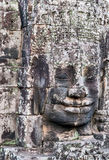 Famous Stone smiling face in Prasat Bayon, part of Angkor. Famous Ancient stone faces of king Bayon Temple Angkor Thom, Cambodia. Ancient monument Khmer Royalty Free Stock Photo