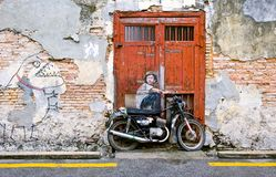 Famous Street Art Mural in George Town, Penang Unesco Heritage Site, Malaysia. Public street art Boy on a Bike on the wall by Lithuanian artist Ernest Zacharevic Royalty Free Stock Photo