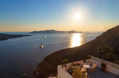 Famous sunset in Santorini, Greece, overlooking the hotel terrace with table and chairs Stock Images