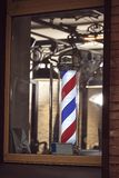 The famous symbol of a barber shop with it swirling red, blue and white stripes. stock photos