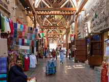 The famous textile souk in Bur Dubai. Shops and vendors in the ancient covered textile souq Bur Dubai in the old city centre of Dubai, United Arab Emirates Royalty Free Stock Photos