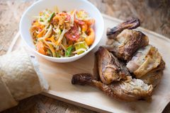 Famous Thai food papaya salad. And grilled chicken on wooden plate selective focus royalty free stock photo