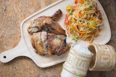Famous Thai food papaya salad and grilled chicken. With sticky rice on wooden plate, selective focus royalty free stock images
