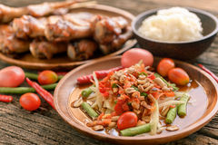 Famous Thai food, papaya salad and grilled chicken. On wooden plate  ,selective focus Royalty Free Stock Photo
