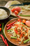 Famous Thai food, papaya salad ,somtum. Green papaya salad Thai cuisine spicy delicious with sticky rice on wooden plate , SomTam royalty free stock photography