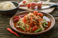 Famous Thai food, papaya salad ,somtum. Green papaya salad Thai cuisine spicy delicious with sticky rice on wooden plate , SomTam stock photo