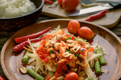 Famous Thai food, papaya salad ,somtum. Green papaya salad Thai cuisine spicy delicious with sticky rice on wooden plate , SomTam stock images