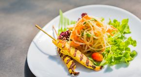 Famous Thai papaya salad or Somtum with Chicken satay on side.  Royalty Free Stock Image