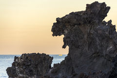 Famous tourist attraction in Jeju island of South Korea. View of Yongduam also known as dragon head rock during sunset. Stock Images