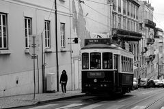 Rising an hill in Lisbon. Famous tram 25 and a young woman rising an hill along a street in Lisbon royalty free stock photography