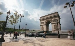 Famous Triumphal Arch, symbol of the glory and historical heritage. Iconic architectural landmark of Paris, France. Charles de Gaulle square. City traffic Royalty Free Stock Photo