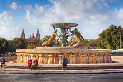 Famous Valetta landmark Triton fountain. VALETTA, MALTA - JANUARY 18 2015: Famous Valetta landmark Triton fountain with locals and tourists nearby Stock Image