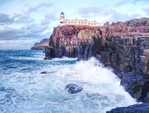 Famous view to Neist Point lighthouse on the end of  world. Foamy sea strikes against cliffs. Famous view to Neist Point lighthouse on the end of  world. Foamy Royalty Free Stock Photo