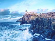 Famous view to Neist Point lighthouse on the end of  world. Foamy sea strikes against cliffs. Famous view to Neist Point lighthouse on the end of  world. Foamy Royalty Free Stock Images