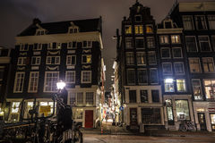 Famous vintage buildings of Amsterdam city at night time. General landscape view at tradition Dutch architecture. AMSTERDAM, NETHERLANDS - JANUARY 10, 2017 Royalty Free Stock Image